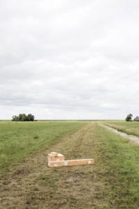 Merel Karhof wind knitting a scarf in a Dutch grass-land